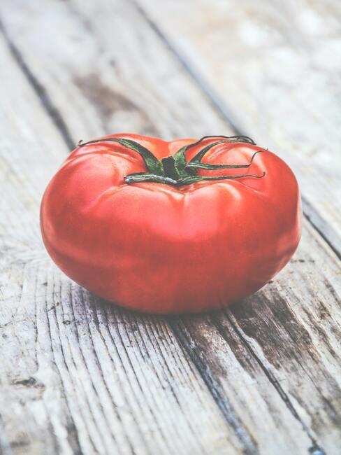 een tomaat op een houten tafel