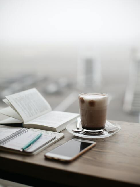 Kop koffie en notitieboekje op werkplek met uitzicht