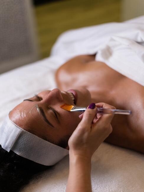 vrouw krijgt gezichtsbehandeling in een spa hotel