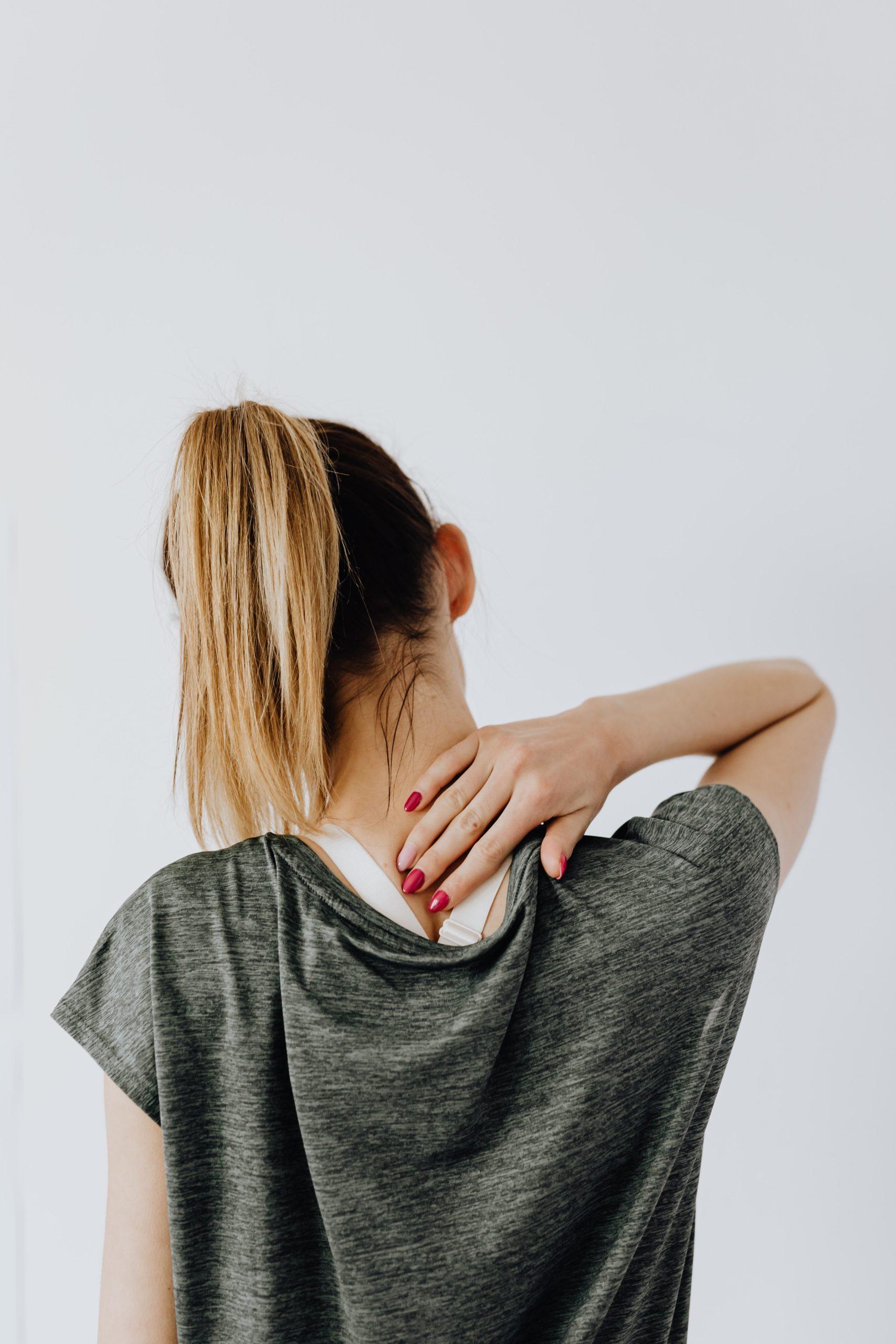 Vrouw wrijft over haar nek omdat ze last heeft van haar rug
