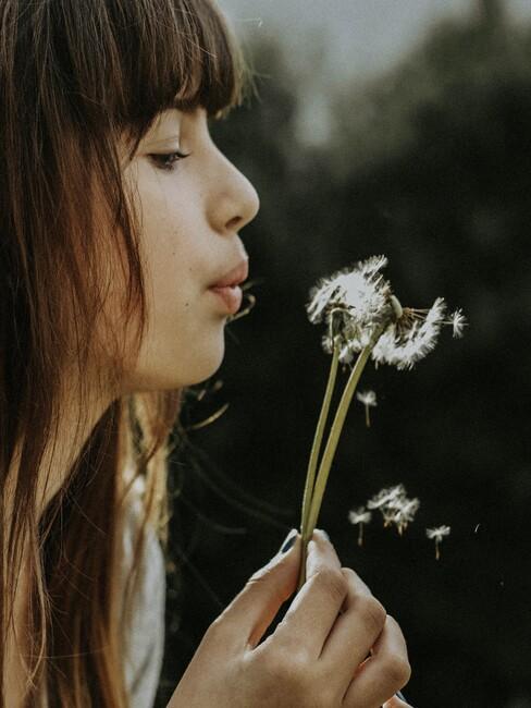 Vrouw blaast de blaadjes van een paardebloem weg