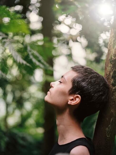 vrouw staat tegen een boom en ademt