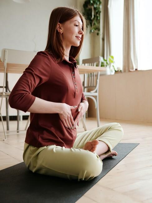 vrouw drukt beide handen op haar buik voor het doen van ademhalingsoefeningen