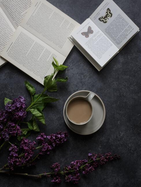 Kopje koffie met schoteltje naast een boek