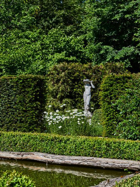 sculptuur in een tuin vol bomen en bloemen