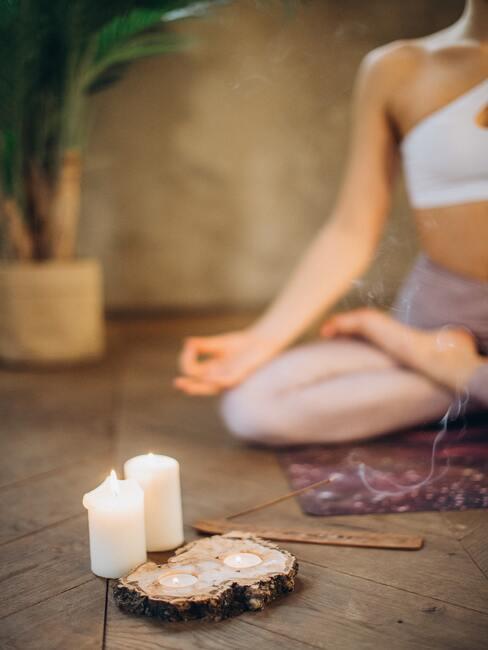 vrouw zit in kleermakerszit op de grond te mediteren met kaarsen