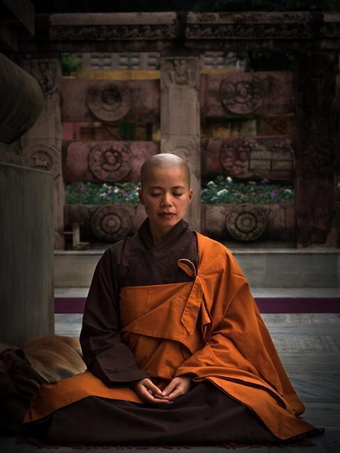Jonge monnik zit in lotushouding te mediteren
