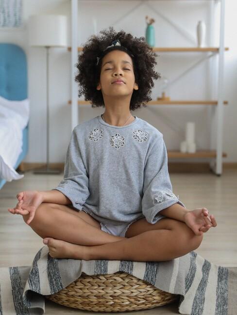 Kind zit op een rieten kussen te mediteren