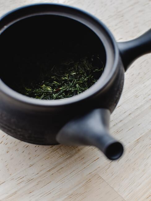 Groene thee bladeren in zwarte kop
