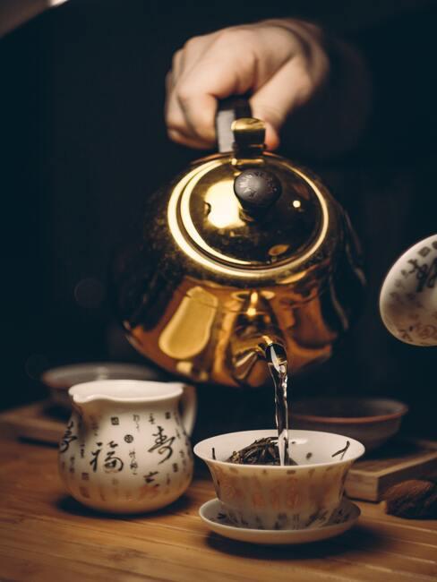warm water wordt over de groene thee bladeren geschonken