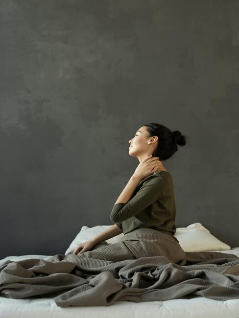 vrouw in bed heeft last van haar rug