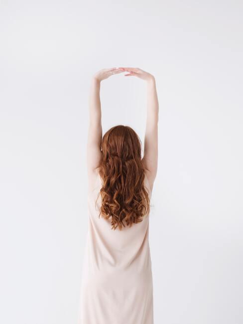 vrouw strekt haar armen uit om rugpijn te voorkomen