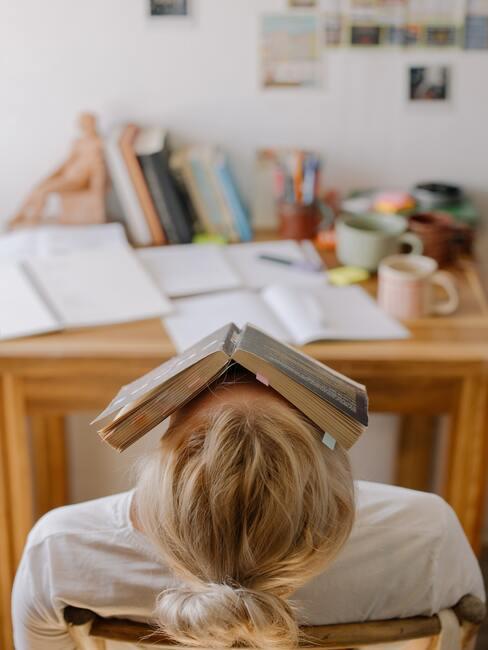 Vrouw valt in slaap achter bureau met boek op haar gezicht