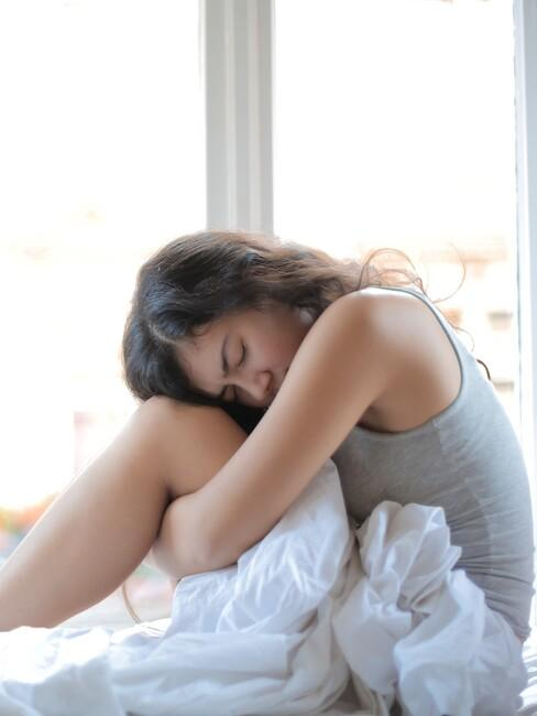 Vrouw zit op bed en heeft last van een winterdepressie