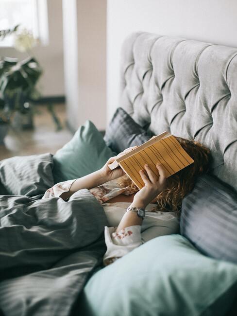 vrouw ligt in bed met boek op haar hoofd is moe