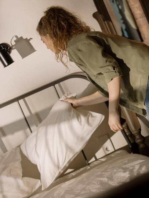 Vrouw haalt hoofdkussen van het bed