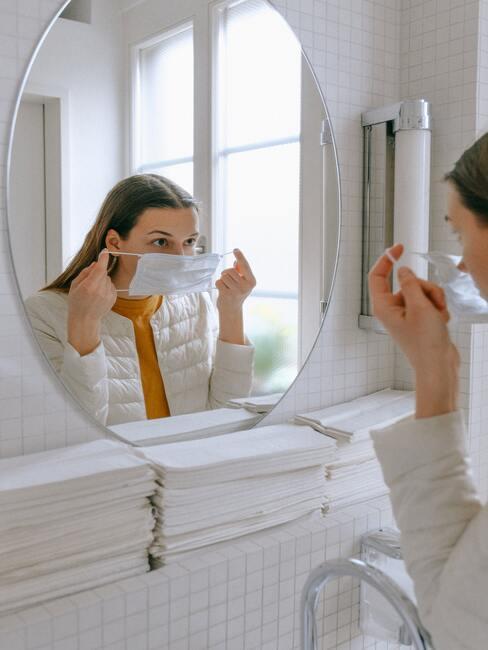 vrouw doet mondkapje voor haar gezicht op een badkamer