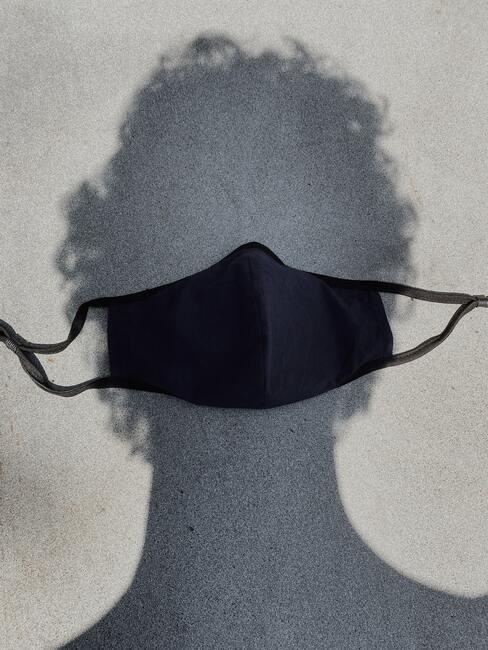 In de schaduw draagt man een zwart mondkapje