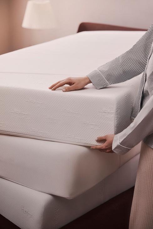 beige bed met een wit matras