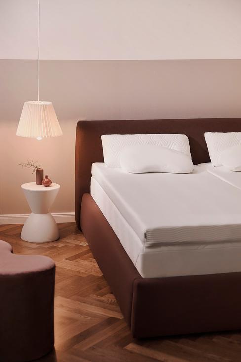 rood bed met een wit matras en een wit nachtkastje