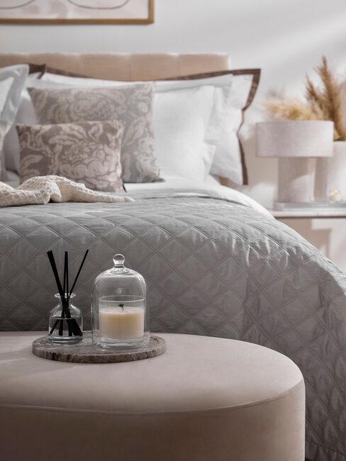 een tweepersoonsbed met grijze plaid