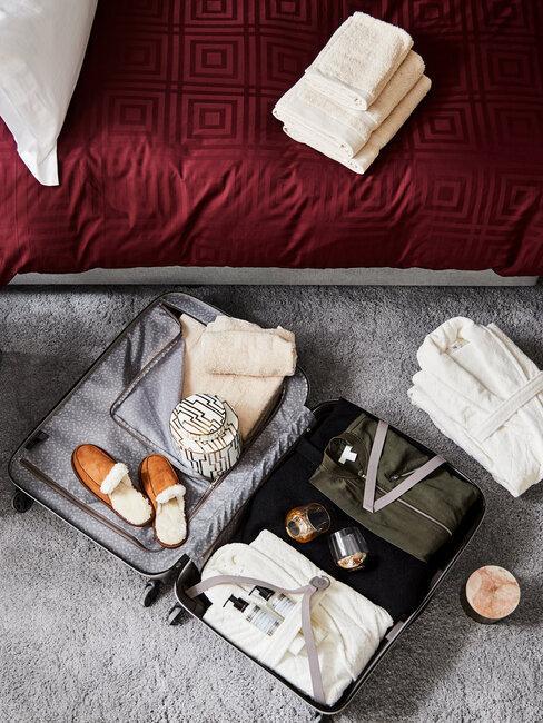 een open koffer op grijze vloerbedekking