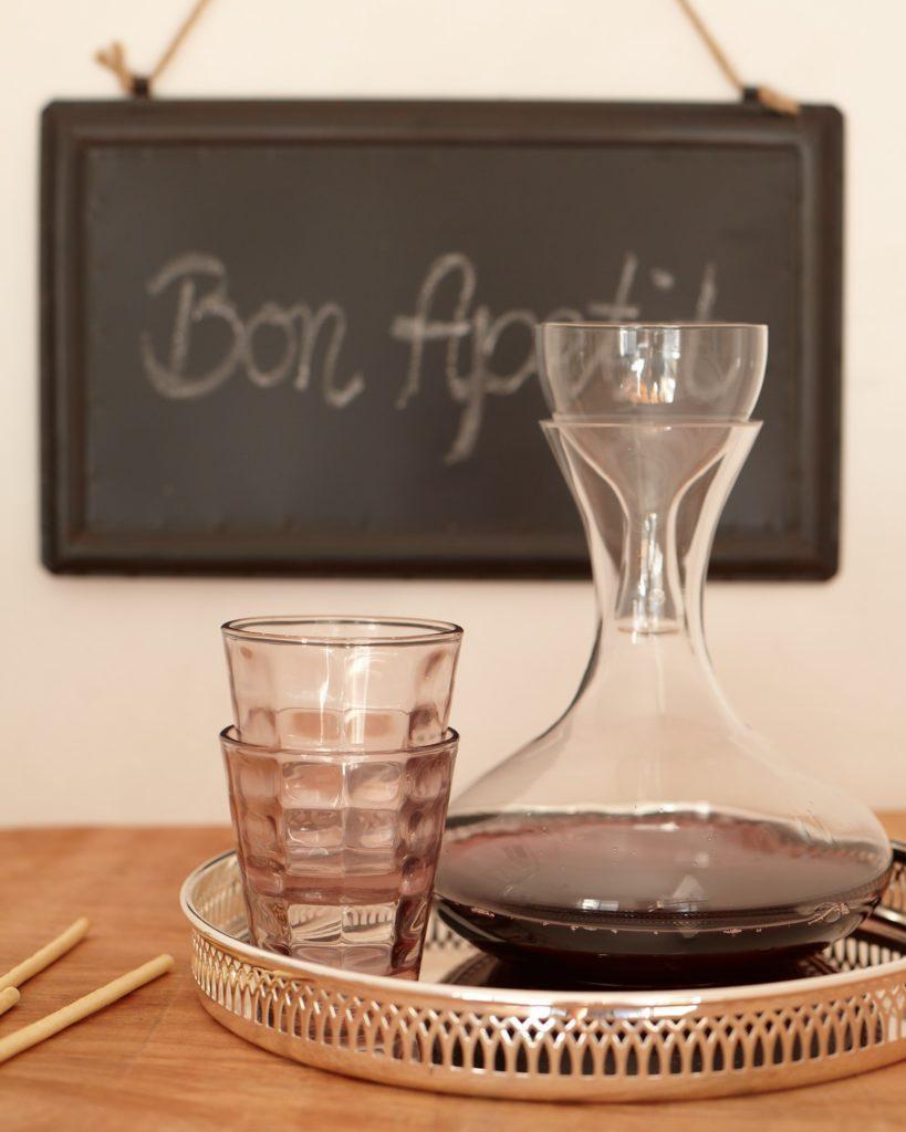 krijtbord bon apetit en dienblad met een karaf met wijn en glazen
