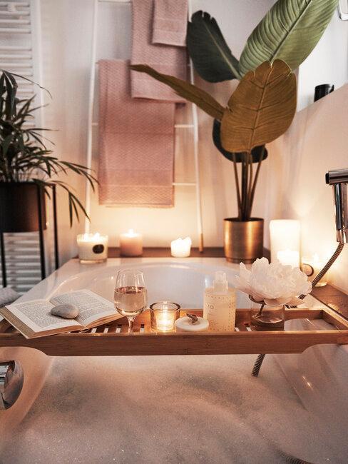 plankje met spa producten en een plant in een gouden pot