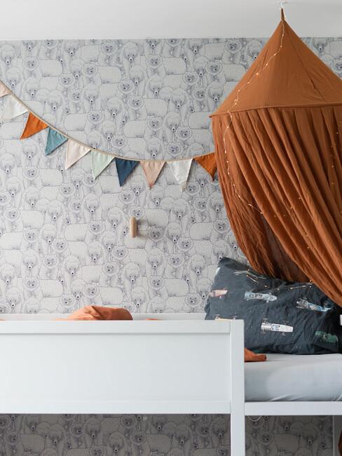 kinderkamer met print behang en terracotta gekleurde klamboe