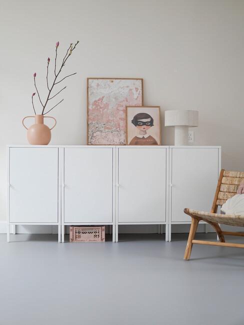 dressoir met roze accessoires en lage rotan stoel