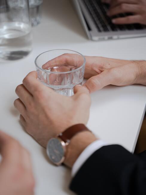 handen met een horloge die een glas water vast hebben