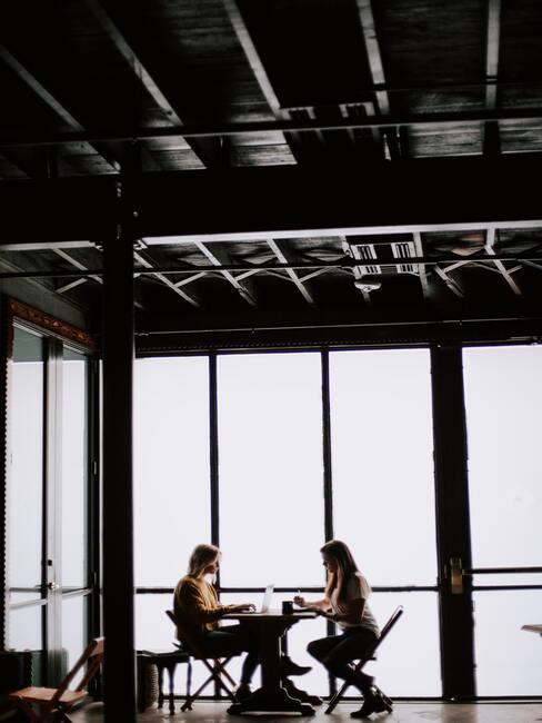 vrouwen in een donkere ruimten aan een tafel