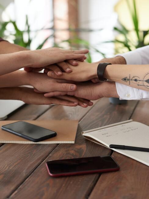 Handen op elaak boven een houten tafel met telefoons