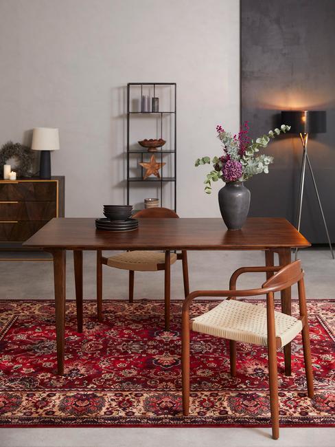 Houten tafel met houten stoelen op rood kleed