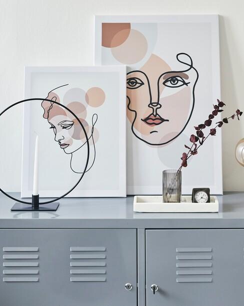 Grijs dressoir met kunst printen in vrouwelijke vromen en ronde zwarte kaarshouder