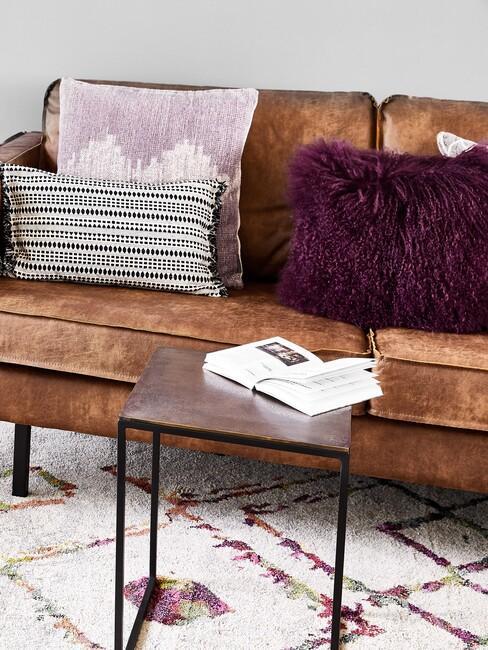 Bruine bank met paarse kussens en bruine bijzettafel