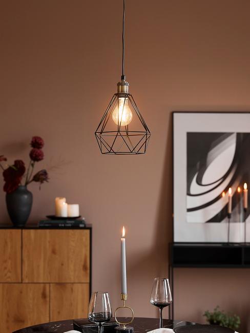 Woonkamer met terracotta wand en zwarte hanglamp