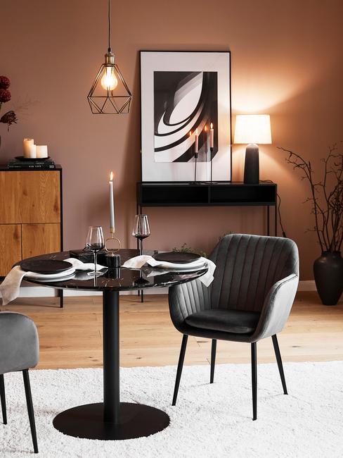 Woonkamer met ronde zwarte eettafel en grijze stoelen