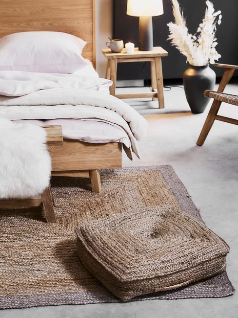 Houten bed met witte lakens en rieten vloerkussen