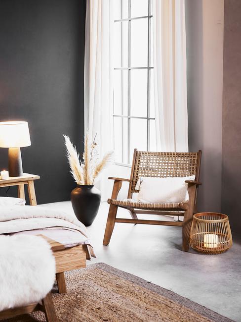Slaapkamer met grijze muur en houten meubels