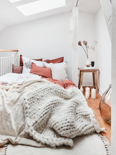 Bed met chunky knit plaid en roze kussens