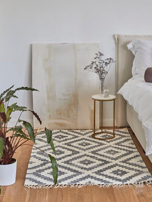 Slaapkamer met geruit vloerkleed, plant en abstract schilderij