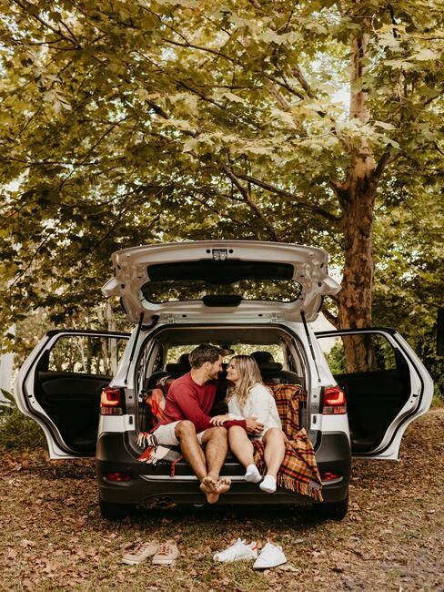 Stel zit in de achterbak van de auto in de natuur te picknicken