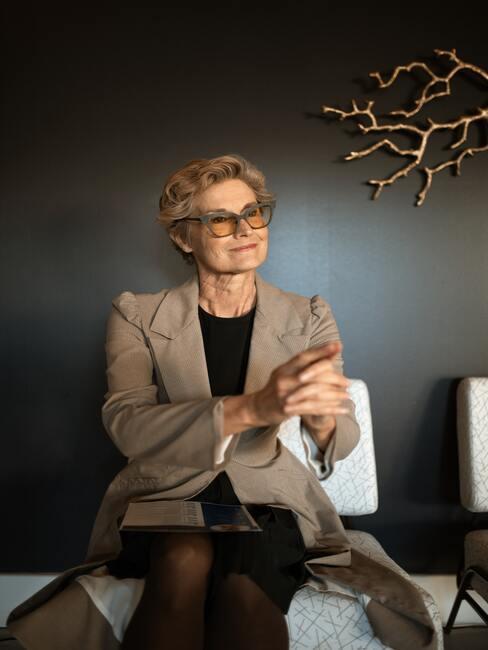 Vrouw met jasje aan op stoel