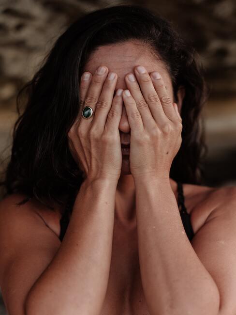 Vrouw met handen in haar gezicht, angst.