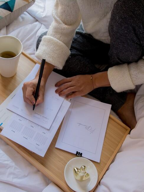 vrouw schrijft notities op in haar notitie blok