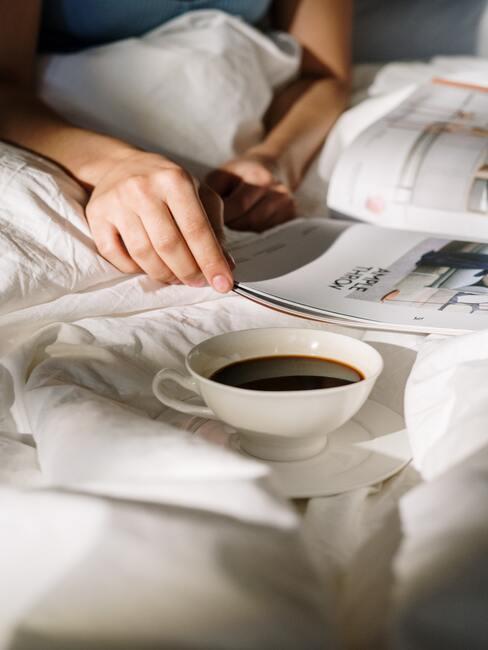 Koffie drinken en een tijdschrift lezen in bed