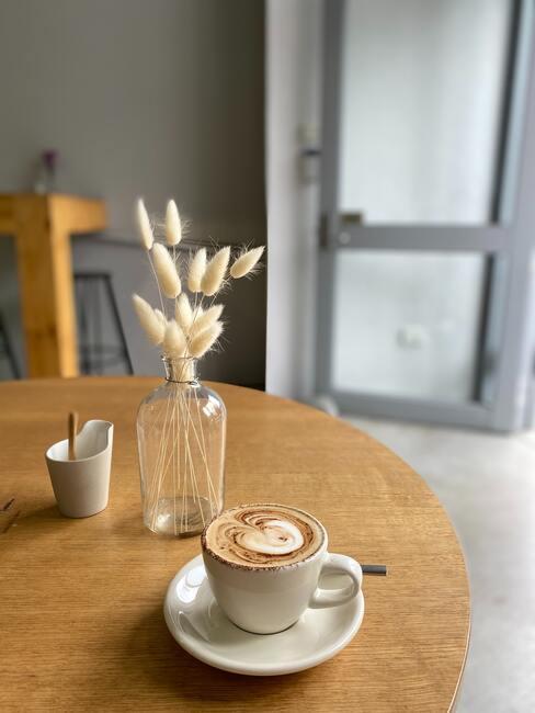 Cappuchino op houten tafel met vaas met droogbloemen