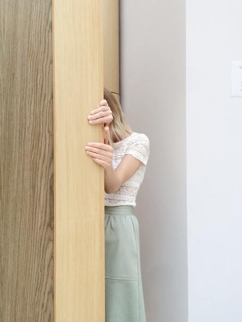 Vrouw verschuilt zich achter een muur