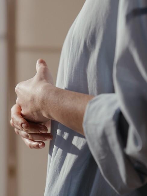 Vrouw staat in de zon met handen over elkaar